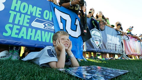 Larry Richardson, 7, of Silverdale, Wash., peers out from under the barricade as he tries to catch a glimpse of his favorite player, Seattle Seahawks quarterback Russell Wilson, on the second day of Seattle Seahawks NFL football training camp, Monday, July 31, 2017, in Renton, Wash. (AP Photo/Ted S. Warren)