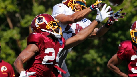 Washington Redskins wide receiver Josh Doctson (18) hauls in a pass in front of cornerback Josh Norman (24) during practice at the Washington Redskins NFL training camp in Richmond,. Va., Monday, July 31, 2017. (AP Photo/Steve Helber)