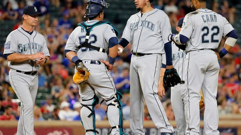 Seattle Mariners manager Scott Servais, left, walks up to take the ball from starting pitcher Felix Hernandez, second from right, as Carlos Ruiz (52) and Robinson Cano (22) stand on the mound in the sixth inning of a baseball game against the Texas Rangers, Monday, July 31, 2017, in Arlington, Texas. (AP Photo/Tony Gutierrez)