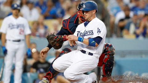 Atlanta Braves catcher Tyler Flowers loses the ball as Los Angeles Dodgers' Yasmani Grandal slides into home plate to score on a ground ball by Yasiel Puig during the sixth inning of a baseball game, Saturday, July 22, 2017, in Los Angeles. (AP Photo/Ryan Kang)