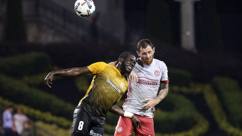 Jun 14, 2017; Atlanta, GA, USA; Atlanta United midfielder Chris McCann (16) heads the ball against Charleston Battery midfielder Reveal Hackshaw (8) in the first half of their game at Fifth Third Bank Stadium. Mandatory Credit: Jason Getz-USA TODAY Sports