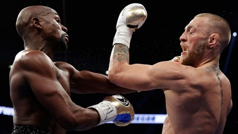 Floyd Mayweather Jr., left, hits Conor McGregor in a super welterweight boxing match Saturday, Aug. 26, 2017, in Las Vegas. (AP Photo/Isaac Brekken)