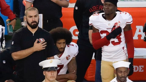 FILE - In this Sept. 1, 2016 file photo, San Francisco 49ers quarterback Colin Kaepernick, center, sits during the national anthem before an NFL preseason football game against the San Diego Chargers in San Diego. The anthem is played before the start of every U.S. major sporting event, where fans and players are expected to salute the flag by placing a hand over the heart while singing along. Not doing so is considered unpatriotic by some. The anthem has also been used by athletes as a way to protest. (AP Photo/Chris Carlson, File)