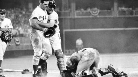 FILE - In this July 14, 1970, file photo, National League's Pete Rose, left, is hugged by teammate Dick Dietz while American League catcher Ray Fosse kneels injured on the ground after he crashed into Fosse to score the winning run for the National League team in the 12th inning of the 1970 All-Star Game in Cincinnati. When a Kansas City employee chased Fosse down requesting he sign alongside Rose on a photo of the collision, the former catcher and current Oakland broadcaster declined. (AP Photo/File)