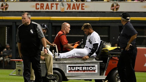 Chicago White Sox second baseman Yoan Moncada, center, is carted off the field after colliding with right fielder Willy Garcia on a double hit by Toronto Blue Jays' Darwin Barney during the sixth inning of a baseball game, Monday, July 31, 2017, in Chicago. Both players left the game. (AP Photo/David Banks)