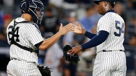 New York Yankees catcher Gary Sanchez (24) celebrates with Yankees relief pitcher Aroldis Chapman (54) after Chapman earned a save in the Yankees 7-3 victory over the Detroit Tigers in a baseball game at Yankee Stadium in New York, Monday, July 31, 2017. (AP Photo/Kathy Willens)