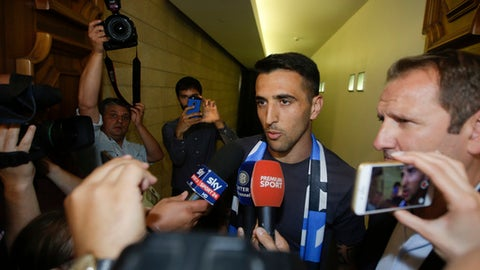 Uruguayan midfielder Matias Vecino is surrounded by reporters at the Inter Milan soccer team headquarters, in Milan, Italy, Tuesday, Aug. 1, 2017.  Vecino has concluded medical exams with Inter Milan and is near to completing a transfer from Fiorentina estimated at 24 million euros ($30 million). (AP Photo/Luca Bruno).
