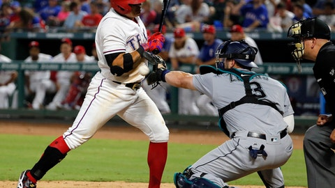 Texas Rangers' Shin-Soo Choo reacts to being hit by a pitch as Seattle Mariners' Mike Zunino (3) reaches for the ball during the sixth inning of a baseball game, Tuesday, Aug. 1, 2017, in Arlington, Texas. Home plate umpire Jeff Nelson watches the play. (AP Photo/Tony Gutierrez)
