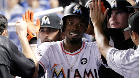Miami Marlins' Dee Gordon is congratulated in the dugout after scoring on a double by Giancarlo Stanton during the first inning of the team's baseball game against the Washington Nationals, Wednesday, Aug. 2, 2017, in Miami. (AP Photo/Lynne Sladky)