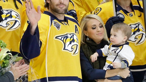 "FILE - In this March 21, 2016, file photo, Nashville Predators forward Mike Fisher is honored for his 1,000th NHL hockey game before the first period of a game against the Los Angeles Kings, in Nashville, Tenn. With Fisher is his wife, singer Carrie Underwood, and their son, Isaiah. Mike Fisher has announced his retirement, a move that means the defending Stanley Cup finalists must select a new captain. Fisher, 37, said in a letter to Predators fans that ""this is the hardest decision that I've ever had to make, but I know I've made the right one.""(AP Photo/Mark Humphrey, File)"
