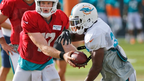 Miami Dolphins quarterback Ryan Tannehill, left, hands off to running back Kenyan Drake an NFL football training camp, Thursday, Aug. 3, 2017, at the Dolphins training facility in Davie, Fla. (AP Photo/Wilfredo Lee)