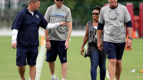 In this June 15, 2017, photo, former Tennessee Titans linebacker Tim Shaw, second from left, leaves the field with Titans general manager Jon Robinson, left, and head coach Mike Mularkey, right, after an organized team activity at its NFL football training facility in Nashville, Tenn. Shaw, who was diagnosed with ALS in 2014, has worked with the special teams staff and players, and has been given a locker in the team's locker room. (AP Photo/Mark Humphrey)