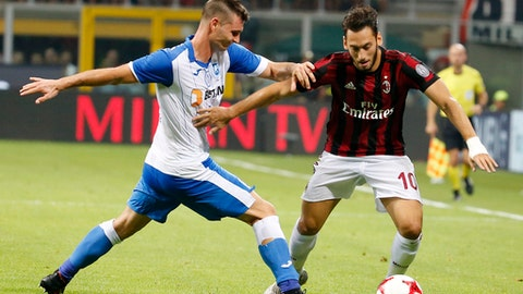 AC Milan's Hakan Calhanoglu, right, challenges for the ball with U Craiova's Hrvoje Spahija during an Europa League third qualifying round, second leg, soccer match at the San Siro stadium in Milan, Italy, Thursday, Aug. 3, 2017. (AP Photo/Antonio Calanni)