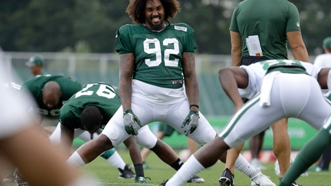 New York Jets nose tackle Leonard Williams, center, laughs while talking to a staff member during NFL football training camp, Friday, Aug. 4, 2017, in Florham Park, N.J. (AP Photo/Julio Cortez)