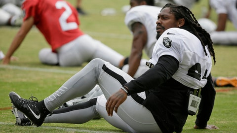 Oakland Raiders running back Marshawn Lynch stretches during an NFL football training camp Friday, Aug. 4, 2017, in Napa, Calif. (AP Photo/Eric Risberg)