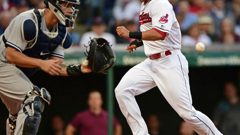 Cleveland Indians' Michael Brantley, right, scores while New York Yankees catcher Gary Sanchez plays the ball in the third inning of a baseball game, Friday, Aug. 4, 2017, in Cleveland. Brantley scored on a sacrifice by Edwin Encarnacion. (AP Photo/David Dermer)