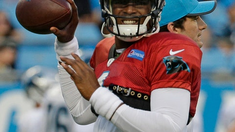 Cam Newton grimaces as he tests his throwing shoulder during practice at the NFL football team's Fan Fest in Charlotte, N.C., Friday, Aug. 4, 2017. Newton did not throw any passes during practice. (AP Photo/Chuck Burton)