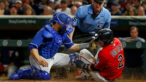 Minnesota Twins' Brian Dozier, right, beats the tag of Texas Rangers catcher Brett Nicholas, left, on a sacrifice fly by Joe Mauer as umpire Ryan Blakney, center, watches in the sixth inning of a baseball game Friday, Aug. 4, 2017, in Minneapolis. (AP Photo/Bruce Kluckhohn)