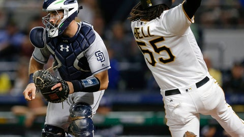 Pittsburgh Pirates' Josh Bell (55) scores on a sacrifice fly by Adam Frazier as San Diego Padres catcher Austin Hedges awaits a throw from center fielder Manuel Margot during the seventh inning of a baseball game, early Saturday, Aug. 5, 2017, in Pittsburgh. (AP Photo/Keith Srakocic)