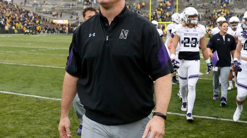 FILE - In this Oct. 1, 2016, file photo, Northwestern head coach Pat Fitzgerald walks off the field after defeating Iowa, 38-31, in an NCAA college football game in Iowa City, Iowa. When it comes to in-game strategy, a six-year-old company named Championship Analytics, Inc., is quickly making a mark. CAI has gone from three schools subscribing to its service in 2014 to 53 this year, including 38 FBS teams. Pat Fitzgerald's Northwestern program is among 22 Power Five conferences schools that have purchased a subscription to CAI's services. (AP Photo/Charlie Neibergall, File)