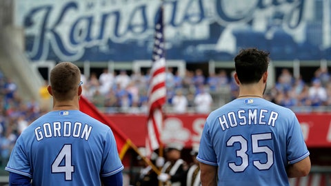 Kansas City Royals' Alex Gordon (4) and Eric Hosmer (35) stand for the national anthem before the first baseball game in a doubleheader against the Seattle Mariners, Sunday, Aug. 6, 2017, in Kansas City, Mo. (AP Photo/Charlie Riedel)