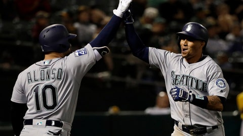 Seattle Mariners' Leonys Martin, right, celebrates his solo home run with teammate Yonder Alonso (10) during the 10th inning of a baseball game against the Oakland Athletics Tuesday, Aug. 8, 2017, in Oakland, Calif. Seattle won 7-6. (AP Photo/Marcio Jose Sanchez)