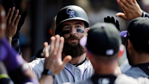 Colorado Rockies' Charlie Blackmon is congratulated by teammates after hitting a solo home run off Cleveland Indians relief pitcher Zach McAllister in the 12th inning of a baseball game, Wednesday, Aug. 9, 2017, in Cleveland. The Rockies won 3-2 in 12 innings. (AP Photo/Tony Dejak)