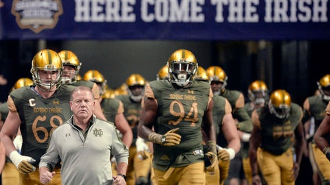 FILE - In this Nov. 12, 2016, file photo, Notre Dame coach Brian Kelly, left, runs onto the field with his players before an NCAA college football game against Army in San Antonio. Safe to say there is not a team in the country more eager to bury the memories of 2016 than Notre Dame.(AP Photo/Darren Abate, File)
