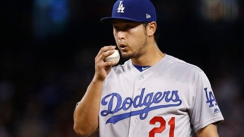 Los Angeles Dodgers pitcher Yu Darvish, of Japan, blows on the baseball during the fourth inning of the team's game against the Arizona Diamondbacks on Thursday, Aug 10, 2017, in Phoenix. (AP Photo/Ross D. Franklin)