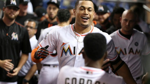Miami Marlins' Giancarlo Stanton, center, celebrates with teammates after he hit a home run during the sixth inning of a baseball game against the Colorado Rockies, Friday, Aug. 11, 2017, in Miami. Stanton hit his Major League-leading 40th home run as the Marlins won 6-3. (AP Photo/Wilfredo Lee)