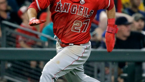 Los Angeles Angels' Mike Trout heads home to score on an error by the Seattle Mariners during the ninth inning of a baseball game Friday, Aug. 11, 2017, in Seattle. (AP Photo/Elaine Thompson)