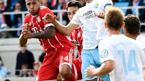 Bayern's Corentin Tolisso, left, challenges for the ball with Chemnitz' Marc Enders, right, during the German soccer cup match between Chemnitzer FC and and FC Bayern Munich in Chemnitz, eastern Germany, Saturday, Aug. 12, 2017. (AP Photo/Jens Meyer)