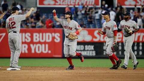 Boston Red Sox's Brock Holt, left, celebrates with teammates Andrew Benintendi, second from left, Mookie Betts and Jackie Bradley Jr., right, after a baseball game against the New York Yankees, Saturday, Aug. 12, 2017, in New York. (AP Photo/Frank Franklin II)