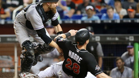 Colorado Rockies catcher Jonathan Lucroy tags out Miami Marlins' Tyler Moore (28) as he slides into home plate during the fourth inning of a baseball game, Saturday, Aug. 12, 2017, in Miami. (AP Photo/Wilfredo Lee)