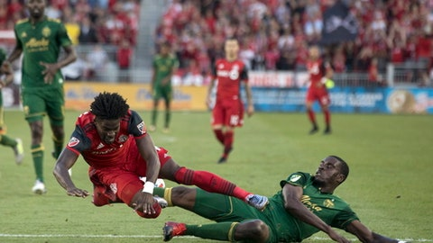 Portland Timbers' Larrys Mabiala, right, tackles Toronto FC's Tosaint Ricketts during the second half of an MLS soccer match Saturday, Aug. 12, 2017, in Toronto. (Chris Young/The Canadian Press via AP)