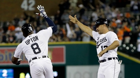Detroit Tigers' Justin Upton (8) is high-fived by first base coach Omar Vizquel after hitting a walk-off two-run home run during the ninth inning of a baseball game against the Minnesota Twins, Saturday, Aug. 12, 2017, in Detroit. (AP Photo/Carlos Osorio)