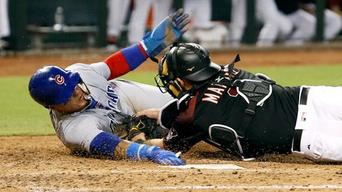 Chicago Cubs' Javier Baez, left, reaches for the plate as he is tagged out by Arizona Diamondbacks catcher Jeff Mathis while trying to score from third base on an infield ground ball by teammate Albert Almora Jr. during the fifth inning of a baseball game, Saturday, Aug. 12, 2017, in Phoenix. The call was upheld by replay after the Cubs challenged the play. (AP Photo/Ralph Freso)