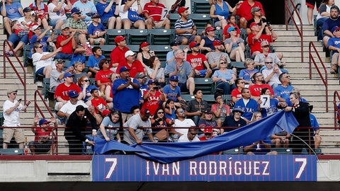 Fans reacts as former Texas Rangers player Ivan Rodriguez's number is retired during a ceremony before a baseball game against the Houston Astros Saturday, Aug. 12, 2017, in Arlington, Texas. (AP Photo/Brandon Wade)