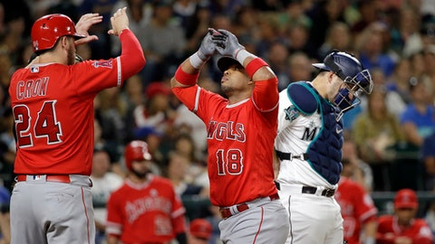 Los Angeles Angels' Luis Valbuena (18) is congratulated on his two-run home run by C.J. Cron as Seattle Mariners catcher Mike Zunino waits during the seventh inning of a baseball game Saturday, Aug. 12, 2017, in Seattle. (AP Photo/Elaine Thompson)