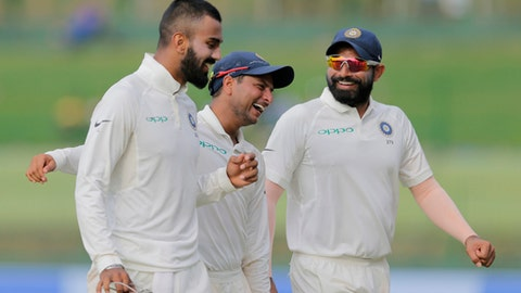 India's Kuldeep Yadav, center, shares a laugh with teammates Mohammed Shami, right, and Lokesh Rahul as they leave the ground at the end of Sri Lanka's first innings on the second day's play of their third cricket test match in Pallekele, Sri Lanka, Sunday, Aug. 13, 2017. (AP Photo/Eranga Jayawardena)