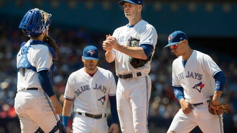 Toronto Blue Jays starting pitcher J.A Happ, second from right, pauses on the mound with teammates in the fifth inning of a baseball game against the Pittsburgh Pirates in Toronto, Sunday, Aug. 13, 2017. (Fred Thornhill/The Canadian Press via AP)