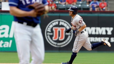 Texas Rangers starting pitcher Andrew Cashner, left, walks to the front of the mound as Houston Astros' Jose Altuve, right, rounds the bases following his solo home run in the fourth inning of a baseball game, Sunday, Aug. 13, 2017, in Arlington, Texas. (AP Photo/Tony Gutierrez)