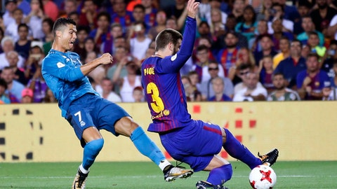 FC Barcelona's Gerard Pique, right, duels for the ball against Real Madrid's Cristiano Ronaldo during the Spanish Supercup, first leg, soccer match between FC Barcelona and Real Madrid at the Camp Nou stadium in Barcelona, Spain, Sunday, Aug. 13, 2017. (AP Photo/Manu Fernandez)