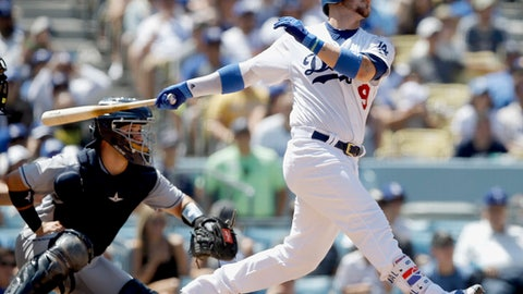 Los Angeles Dodgers' Yasmani Grandal, right, follows through on his two-run home run with San Diego Padres catcher Austin Hedges watching during the fourth inning of a baseball game in Los Angeles, Sunday, Aug. 13, 2017. (AP Photo/Alex Gallardo)
