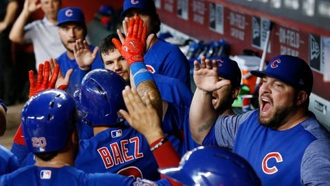 Chicago Cubs' Javier Baez, second from left, celebrates his three-run home run against the Arizona Diamondbacks with Victor Caratini (20), assistant hitting coach Eric Hinske, right, and other teammates during the eighth inning of a baseball game Sunday, Aug 13, 2017, in Phoenix.  (AP Photo/Ross D. Franklin)