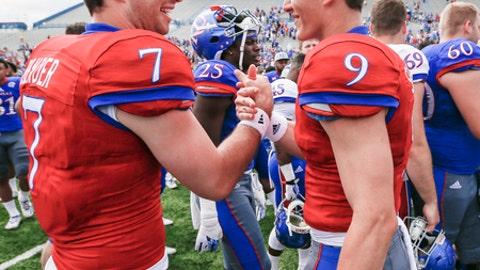FILE - In this April 15, 2017, file photo, University of Kansas quarterbacks Peyton Bender (7) and Carter Stanley (9) shake hands after the 2017 spring football game, in Lawrence, Kan.  The two quarterbacks competing for the starting job at Kansas happen to be roommates and best of friends. But lest anybody think that could be awkward, talk for a bit with sophomore Carter Stanley and junior college transfer Peyton Bender. (Nick Krug/Lawrence Journal-World via AP, File)/The Lawrence Journal-World via AP)