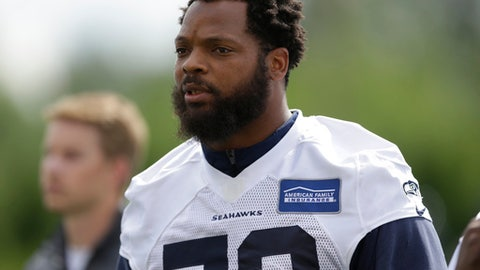 "FILE - In this June 13, 2017, file photo, Seattle Seahawks defensive end Michael Bennett walks off the field following NFL football practice in Renton, Wash. Bennett says he will sit during the national anthem this season to protest social injustice and segregation. Bennett sat on the visiting bench during ""The Star-Spangled Banner"" on Sunday, Aug. 13, 2017, before the Seahawks' preseason opener against the Los Angeles Chargers, a decision he made prior to protests by white supremacists at the University of Virginia over the weekend. But what happened in Charlottesville, Virginia, including the death of a young woman when she was struck by a car deliberately driven into a group of counter-protesters on Saturday, solidified Bennett's decision. (AP Photo/Ted S. Warren, File)"