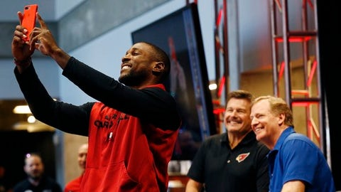Arizona Cardinals cornerback Patrick Peterson, left, shoots a photo with Cardinals president Michael Bidwill, second from right, and NFL football Commissioner Roger Goodell, right, during a session with Cardinals season ticket holders at the University of Phoenix Stadium Monday, Aug. 14, 2017, in Glendale, Ariz. (AP Photo/Ross D. Franklin)