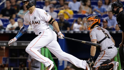 Miami Marlins' Giancarlo Stanton, left, watches his single during the fourth inning of a baseball game against the San Francisco Giants, Monday, Aug. 14, 2017, in Miami. Giants catcher Nick Hundley, right, looks on. (AP Photo/Lynne Sladky)