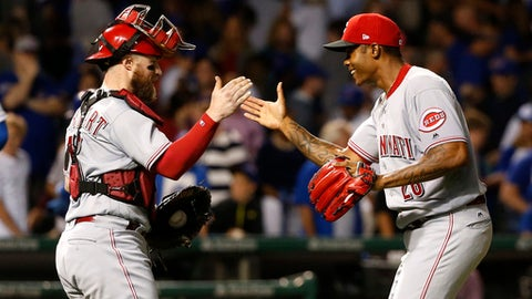 Cincinnati Reds catcher Tucker Barnhart, left, and relief pitcher Raisel Iglesias celebrate the team's 2-1 win over the Chicago Cubs after a baseball game Tuesday, Aug. 15, 2017, in Chicago. (AP Photo/Charles Rex Arbogast)